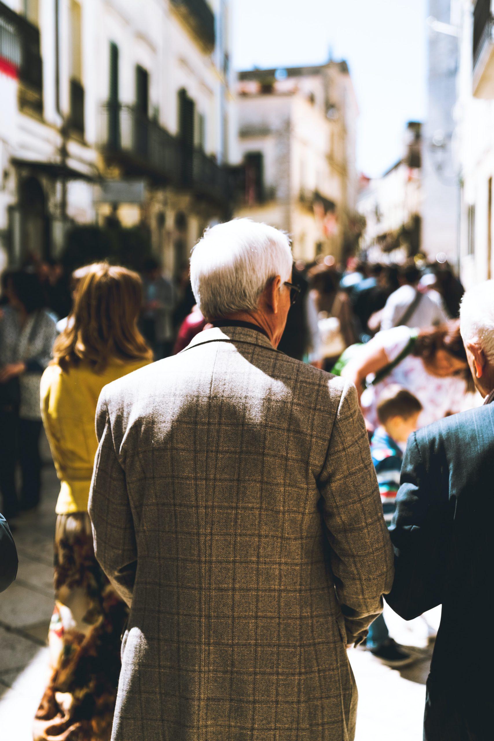 Ein alter, weißer Mann auf der Straße von hinten.