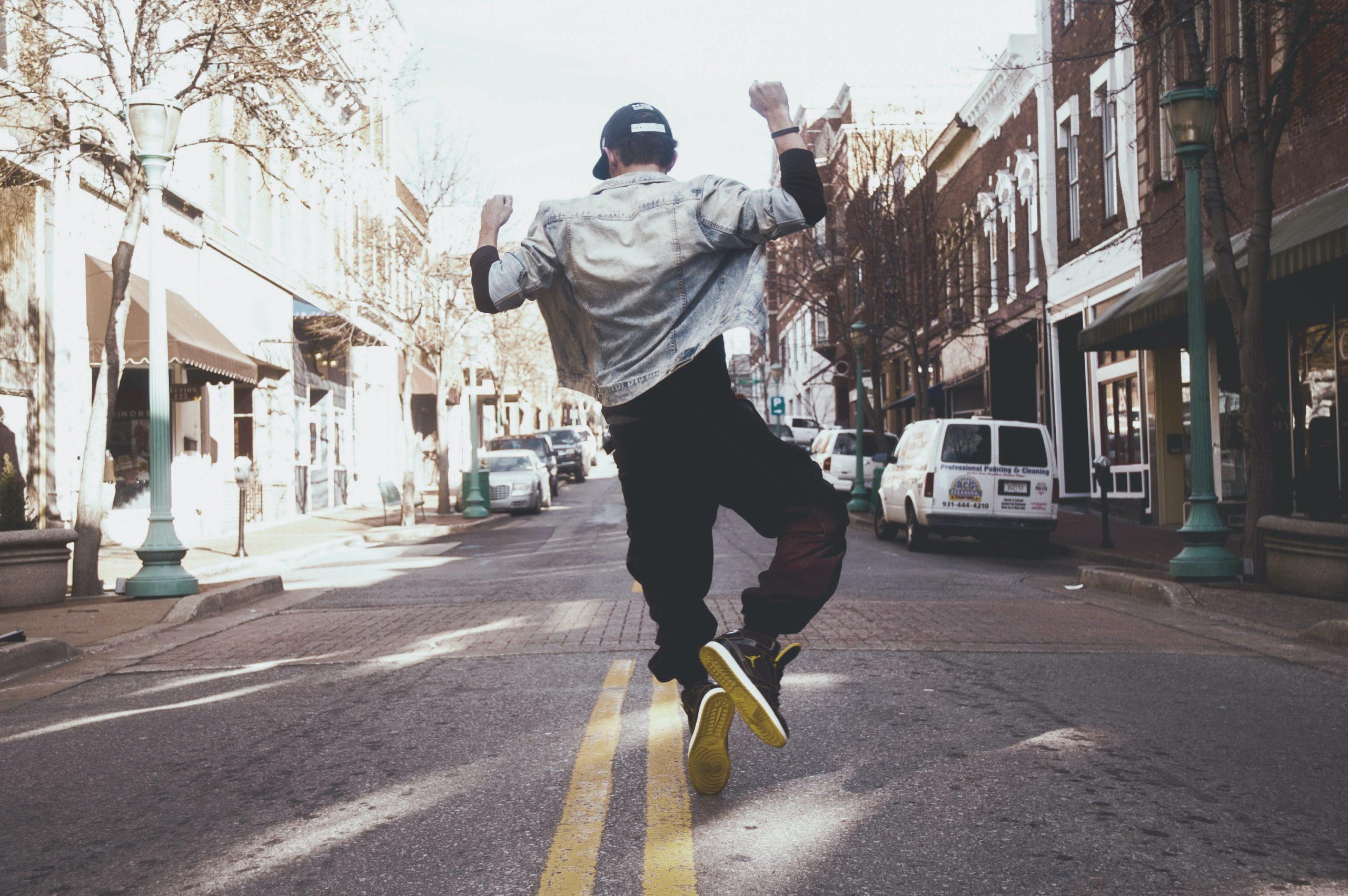 Trotz Corona: Ein junger Mann auf einer Straße ist von hinten zu sehen. Er springt freudig in die Luft.